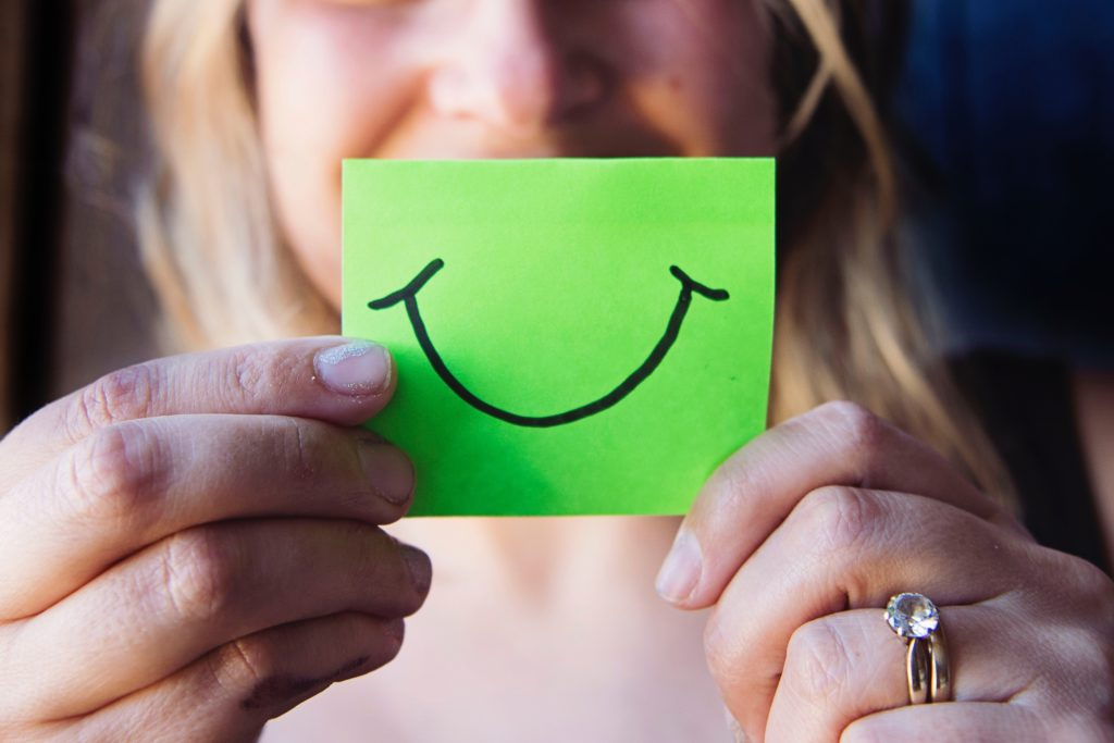 woman holding green paper with smiley face